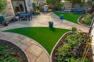 Garden design, patio, paths, artificial grass & landscaping by Stow Construction & Landscaping in Morningside Grove, Edinburgh 2018 using Marshalls Fairstone Riven Harena Golden Sand, Marshalls Fairstone Riven Harena Golden Sand new circle, Marshalls Tegula Drivesett Harvest, Weatherpoint Buff 365, Marshalls Fairstone Sawn Vesuro bull-nosed step units, Namgrass, Marshalls Drivesett kerbs Harvest