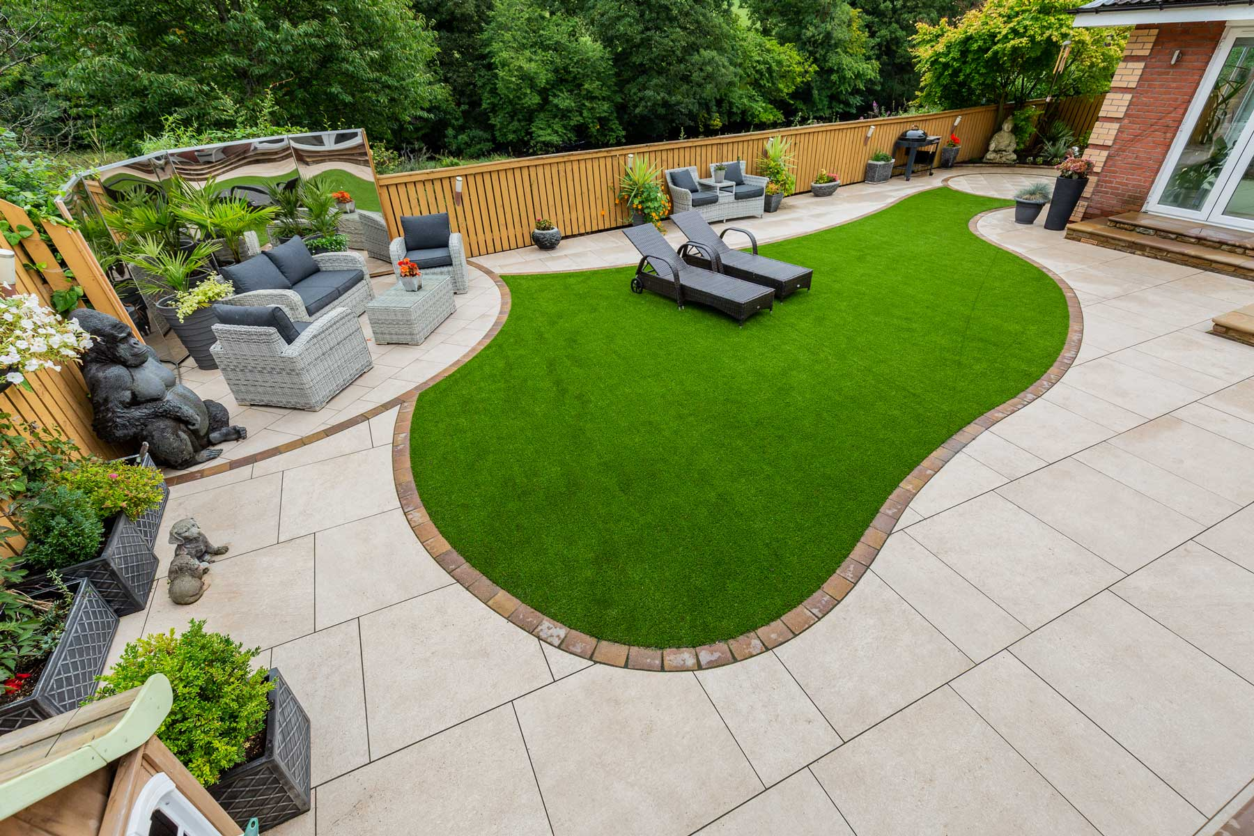 Patio, steps, artificial grass & landscaping by Stow Construction & Landscaping in Smithycroft, Hamilton 2018 using Marshalls Symphony Vitrified Buff, Drivesett Savannah Autumn, Fairstone Sawn Versuro bull-nosed steps Golden Sand, Fairstone walling Autumn Bronze, Evergreen Village Green 30mm artificial grass.