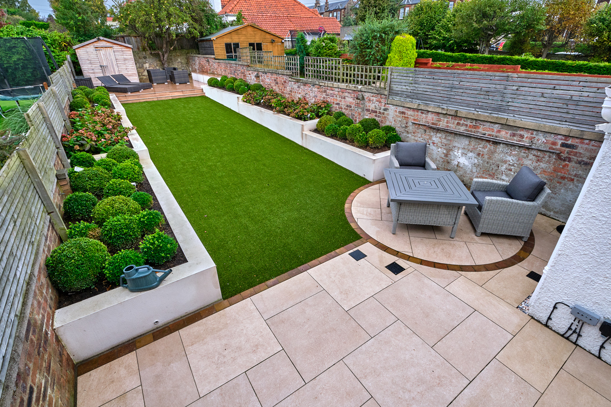 Patio, walling, steps, artificial grass and landscaping designed and installed by Stow Construction & Landscaping, Marshalls Always Green, Summer Lawn, Symphony Vitrified, buff, Drivesett Savannah, Autumn, topsoil, limited access, landscaping, paving, designer, installer, Edinburgh